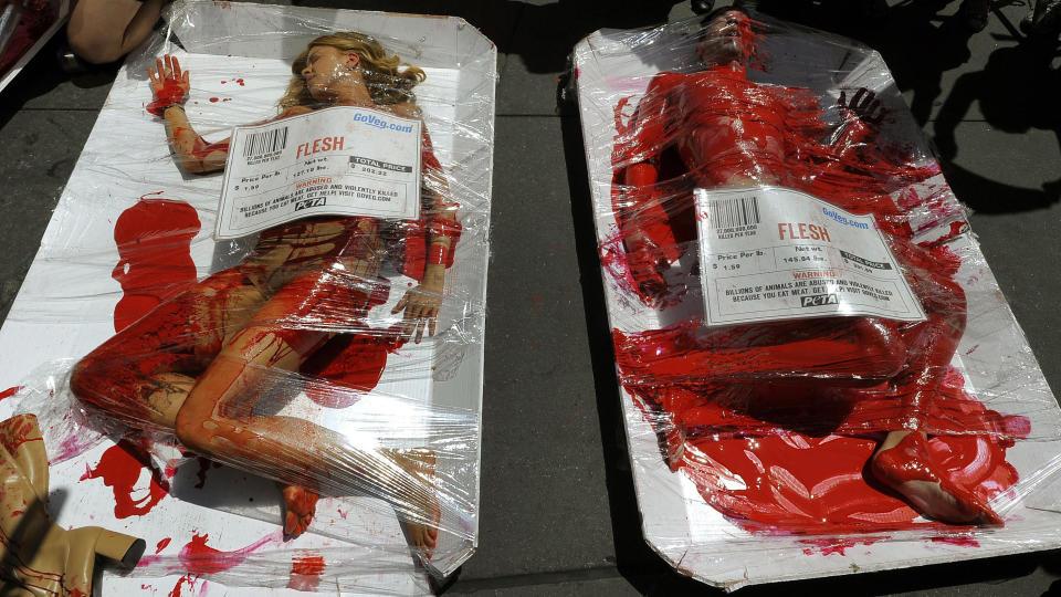 BLODIG: Dyreverne pakket inn i sellofan og smurt inn i kunstig blod under en demstrasjon i New York. FOTO: TIMOTHY A. CLARY/AFP PHOTO/SCANPIX