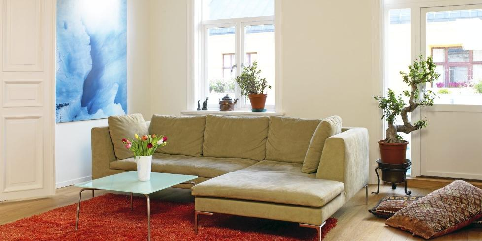 MØBLERING: Sofaen trenger ikke stå helt inntil veggen. Store puter kan også fungere som sitteplasser. Foto: Espen Grønli