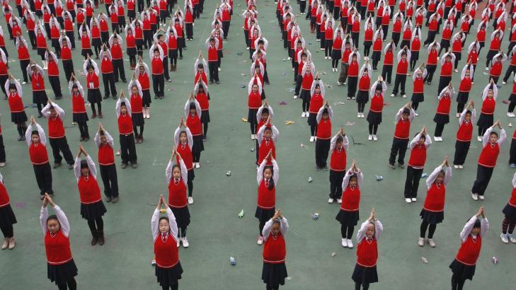YOGA-DISIPLIN: Elever driver yogaøvelser på rekke og rad i et frikvarter ved en barneskole i Suining i provinsen Sichuan i de midtre delene av Kina. Undervisningen i kinesiske skoler skjer i svært disiplinerte former, elevene forventes å pugge hardt, og de gjør det da også godt på de internasjonale PISA-undersøkelsene. Foto: REUTERS / SCANPIX