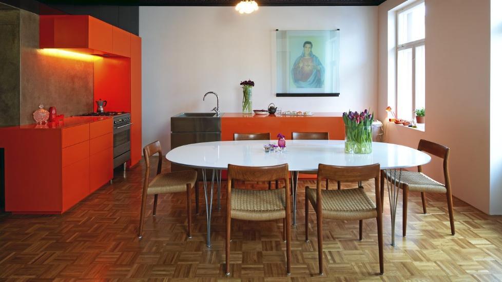 KULE KONTRASTER:  Den mandarinfargete innredningen tegnet av beboerne er laget av kunststoffet corian og mdf-plater. Brettskrurt betongvegg over arbeidsbenken. Overskap av brune forskalingsplater. Stoler kj�pt p� lauritz.com. Designbord fra Fritz Hansen. Det originale parkettgulvet ble beholdt. Elvis-bildet laget eierne selv.   FOTO: Espen Gr�nli
