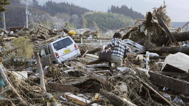 HARDT RAMMET: En beboer prøver å ta seg fram i de ødelagte områdene i byen Rikuzentakata. Her er det funnet mellom 300 og 400 omkomne. Foto: AP Photo/Kyodo News