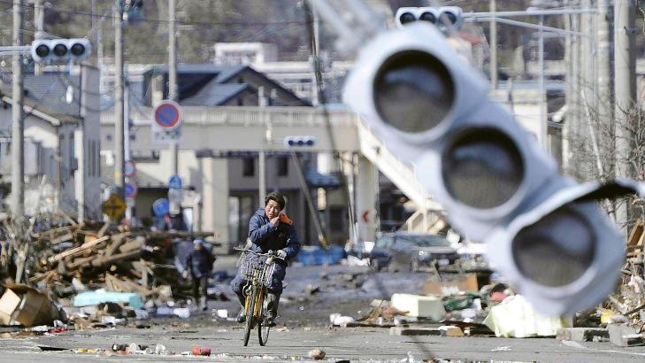 PÅ SYKKEL: En mann sykler langs ødelagte gater i byen Miyako. Foto: AP Photo/Kyodo News