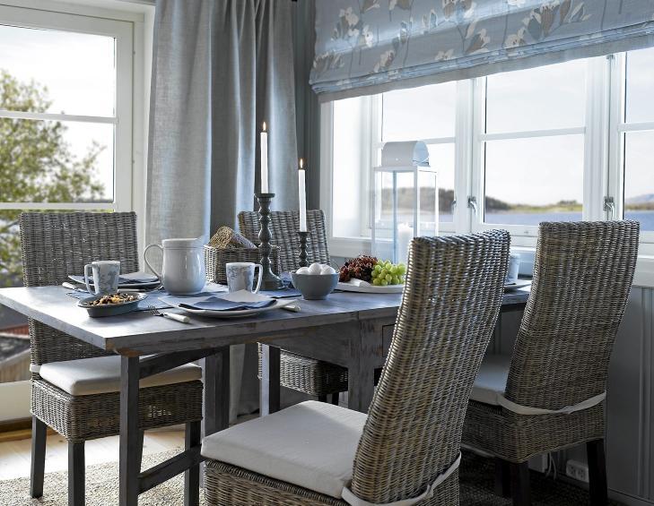 STILIG SOMMERHYTTE Spisestue på en Sande sommerhytte. Rustikt spisebord med kurvstoler og pådekning. Blåmalte vegger og blåmønstrete gardiner. FOTO: Per Erik Jæger