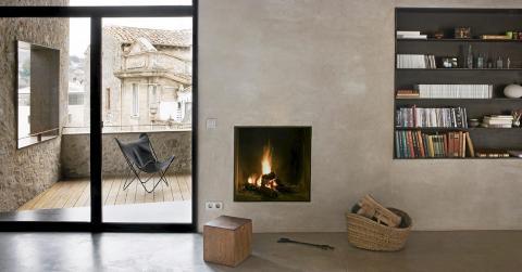 ILDSTED: I stuen gir en tøff peis i minimalistisk stil varme til de ellers kalde veggene.  FOTO: Enric Duch