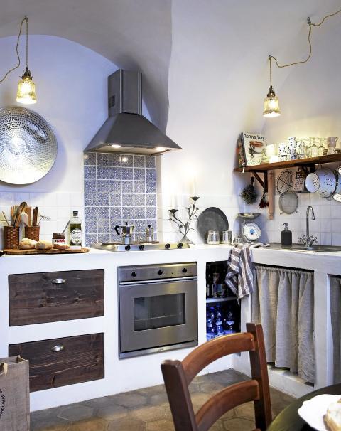 MUR OG FLIS: Murerne tok seg frihet til å flislegge kjøkkenbenken med overskuddsfliser. Fremfor å hakke dem løs valgte Juni og Lars heller å fortsette å flislegge oppover sprutsonen. Dekorflisene bak komfyren er håndlagde. Lampene er fra Bolina, og stålfatet fra Ikea. Foto: Margaret M. de Lange
