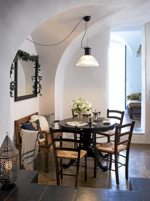 GJENNOMLYS: Fra inngangsdøren ser man gjennom spiseplassen, stua og ut i det fri. Det runde bordet er kjøpt hos en lokal brukthandel, mens de tradisjonelle stolene er nye. Benken er indonesisk, mens lykt og taklampe er kjøpt i San Remo. © Foto: Margaret M. de Lange