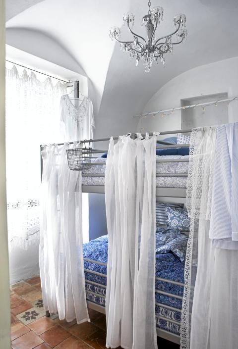 KOMPAKT SØVN: Sengeinstallasjonen består av to spinkle køyesenger fra Ikea. Lette gardiner luner og gir dessuten et preg av himmelseng. Sengetepper fra Anouska. Prismekronen var rusten og stygg da de fikk den av en snill nabo. Etter en runde med såpevann og sølvspray ble den som ny. Foto: Margaret M. de Lange