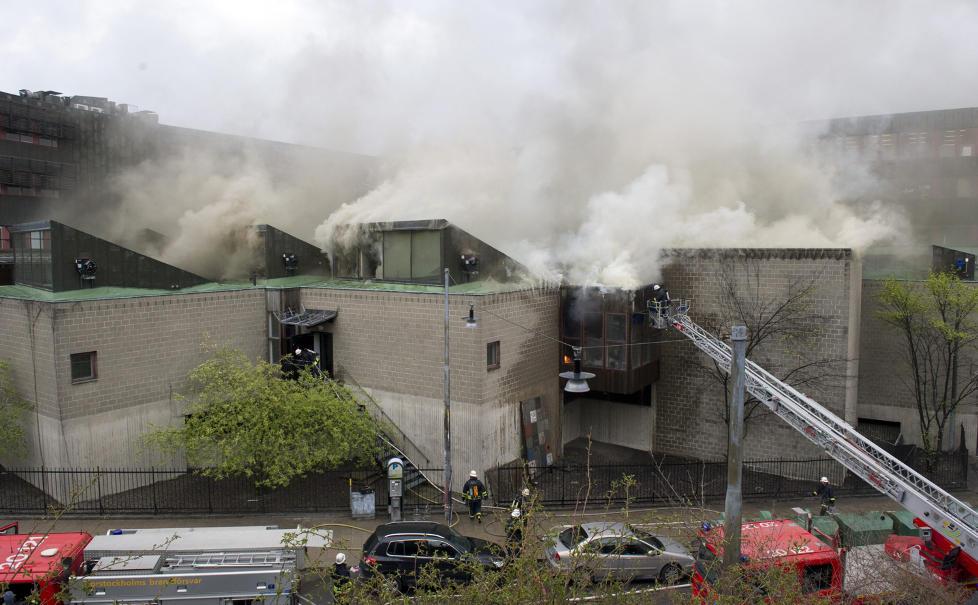 RØYKLEGGER STOCKHOLM: Aulaen på Arkitekturskolan står i full fyr, og røyken fra brannen har spredt seg til store deler av den svenske hovedstaden. Foto: MAJA SUSLIN/SCANPIX