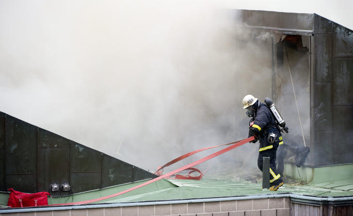 SPRENGTE HULL: Brannmannskapene har sprengt hull i taket på aulaen, for å slippe ut lettantennelige gasser. Foto: MAJA SUSLIN/SCANPIX
