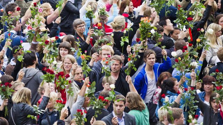 L�FTET ROSENE:  Rundt 200 000 mennesker samlet seg med roser samler seg ved Oslo r�dhus i kveld.. Foto: Vegard Gr�tt / Scanpix