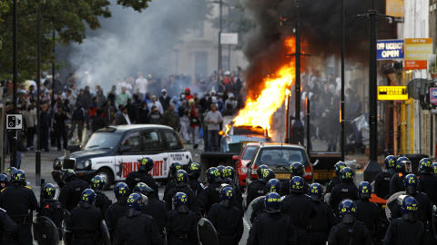 BILER I BRANN: B�de politibiler og vanlige biler er satt i brann flere steder. Foto: REUTERS/Luke MacGregor/Scanpix