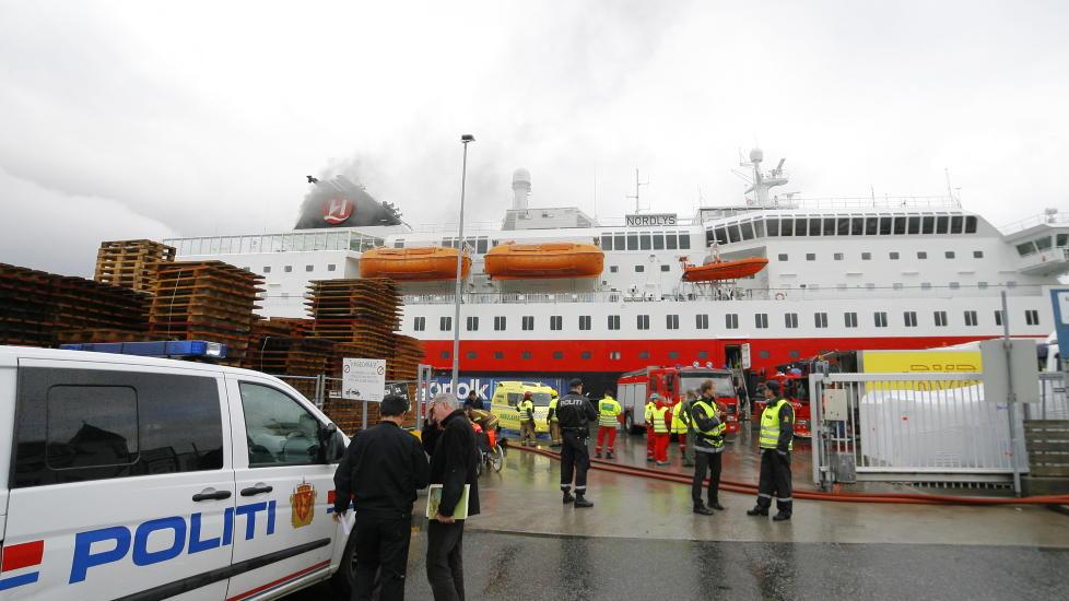 EVAKUERES: Hurtigruta brenner ved kai i Ålesund. Tolv personer er brakt til sykehus etter brannen.  Det brenner fortsatt i hurtigruteskipet, og fire personer er savnet. Foto: Svein Ove Ekornesvåg / Scanpix