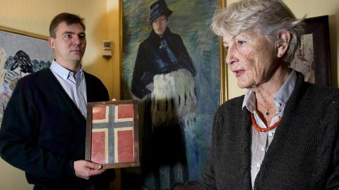 FAMILIEMINNE: Annie de Mora (79) og s�nnen Erik studerer det norske flagget som fulgte Robert F. Scotts ekspedisjon til Sydpolen. I bakgrunnen henger portrettet av Annies mormor som sydde flagget og ga det til Tryggve Gran, som var skiinstrukt�r for Robert F. Scotts ekspedisjon til Antarktis. Foto: �istein Norum Monsen / DAGBLADET