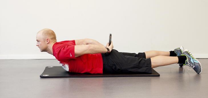 JORDA RUNDT: Ligg p� ryggen og l�ft overkroppen fra underlaget. Bruk en ganske lett vektskive i starten, denne �velsen er tung. F�r skiven fra venstre til   h�yre og bak ryggen tilbake til venstre h�nd.  Trener muskler langs hele ryggs�ylen, korsrygg og rotasjonsmuskler i skulder. Foto: Elisabeth Sperre Alnes