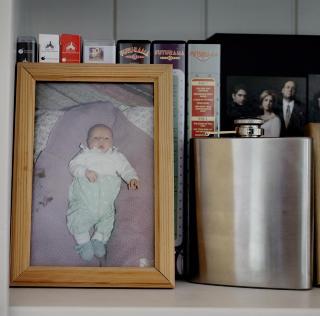 Midt imellom: Ikke helt barn, ikke helt voksen: Babybilde og lommelerke side om side i bokhylla.