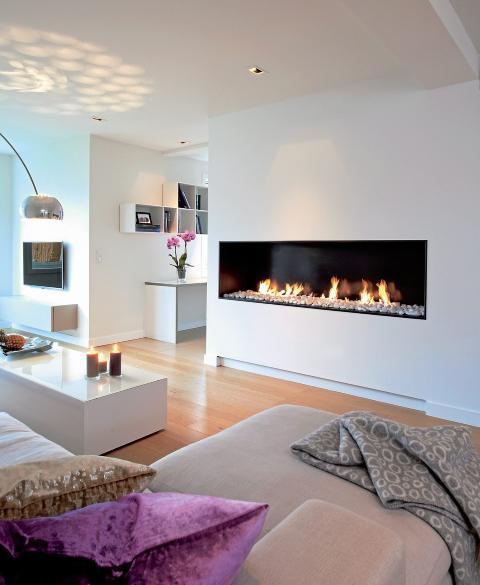 VARMT VEGGMALERI: Den avlange peisen strekker rommets lange linjer, den er dekorativ med flammer mot hvit bakgrunn. Gasspeisen er fra Romerike Peis og Varme. FOTO: Espen Grønli