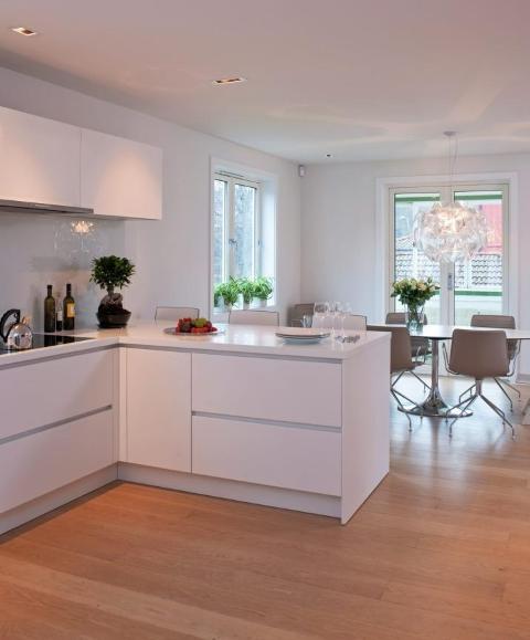 LYS HOVEDFARGE: Kjøkkenbenken fortsetter ut i en halvøy, der frokosten ofte nytes. Hvitevarer er integrert og skjult bak hvite dører. Hvitt er for øvrig husets hovedfarge. FOTO: Espen Grønli