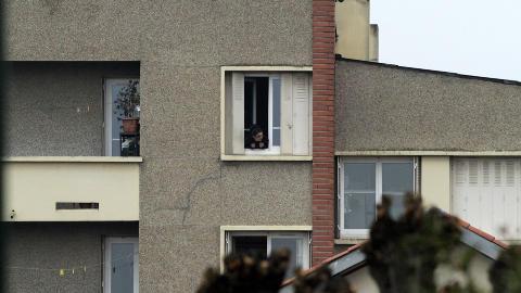 NABOENE SPERRET INNE:  En nabo f�lger politiet, som har omringet huset hvor 24 �r gamle Mohammed Mohammed Merah befinner seg med flere v�pen. Foto: Jean-Philippe Arles  / Reuters