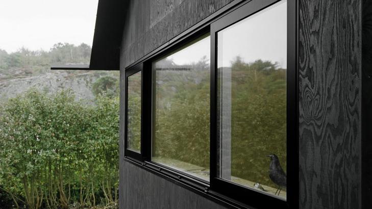 ET HUS MED RENE LINJER: Vinduene g�r som lange, sammenhengende b�nd i fasaden. Legg merke til den spesielle utstikkende takrenna i aluminium. Foto: Rasmus Norlander