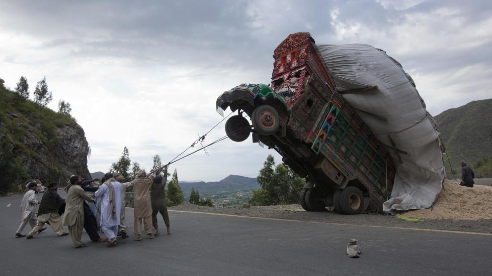 TAUTREKKING: Pakistanske menn jobber alt de kan med � f� rettet opp igjen lastebilen som veltet som f�lger av tung last i Malakand-distriktet i Pakistan, rundt 165 kilometer nordvest for hovedstaden Islamabad. Hendelsen skjedde fredag 13.april 2012. FOTO:  REUTERS/Mian Khursheed