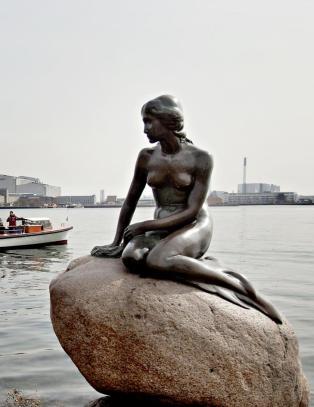 Hun sitter der liten, m�rk og naken p� en stein ute i vannet