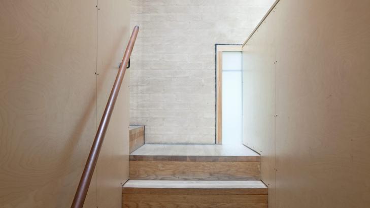 KULT MED KRYSSFINER: Flere av de mindre rommene i huset er kledd med vakre og slitesterke kryssfinerplater. Her ser du trappen som leder opp til den lange, smale buegangen i annen etasje.  Foto: Sandra Aslaksen