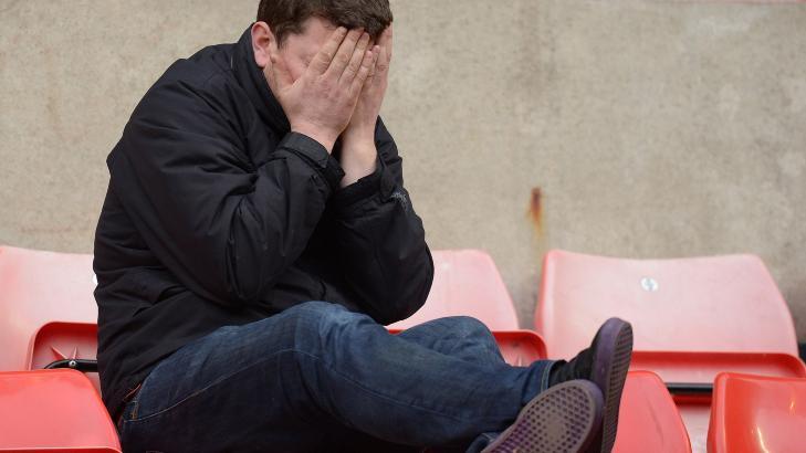 FORTVILELSE: Mens City-supporterne stormet banen i lykkerus, ble United-fansen sittende igjen og deppe etter at ligagullet r�k p� overtid. Foto:  AFP PHOTO/ANDREW YATES