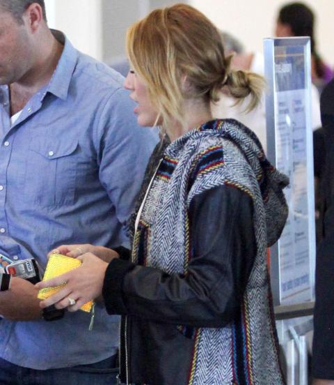 UT P� TUR:  Det er ikke vanskelig � spotte den store diamantringen p� Mileys finger. Foto: Stella Pictures