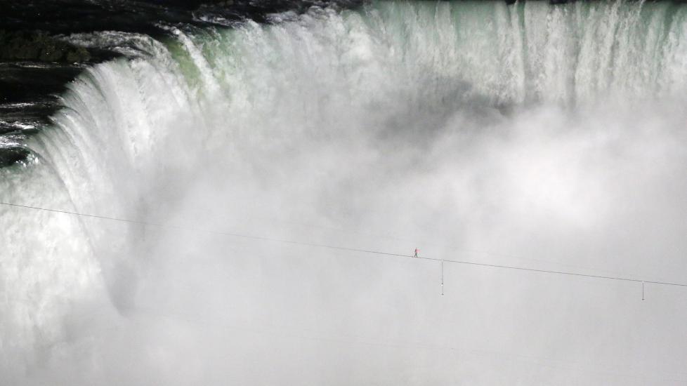 BALANSERER OVER NIAGARAFOSSEN: Amerikanske Nik Wallenda balanserte p� stram line over den ber�mte Niagarafossen p� grensen mellom USA og Canada. Turen over var p� 550 meter og tok mindre enn 30 minutter � utf�re. Foto: MARK BLINCH / REUTERS / NTB SCANPIX