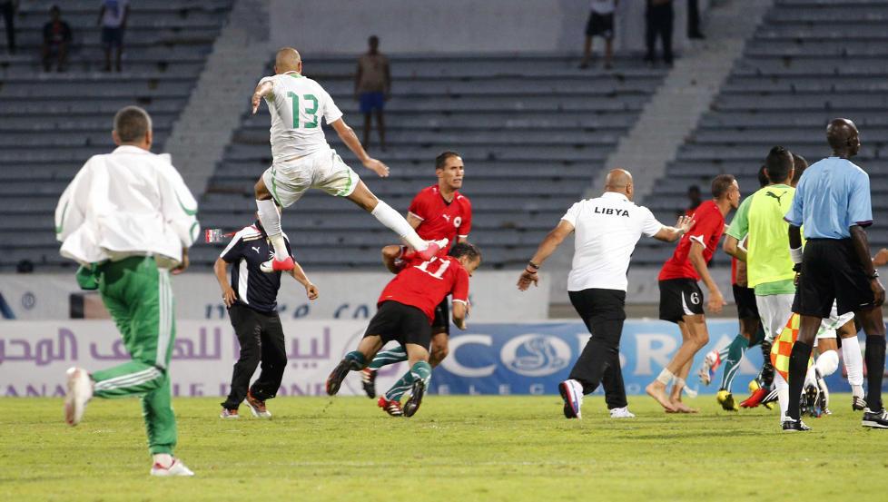 STYGT ANGREP: Algeries Islam Slimani hopper opp og sparker Libyas Mohamed El Mughrabi etter kvalifiseringskampen til afrikamesterskapet p� s�ndag. Foto: MACAO / REUTERS / NTB SCANPIX