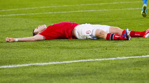 REISTE SEG: John Arne Riise så helt overveldet ut etter å ha gitt Norge 2-1-seier over Slovenia på Ullevaal. Etter kampslutt sank han sammen med lagkameratene over seg. Foto: Vegard Grøtt / NTB scanpix