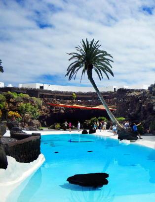 Ute av hulen stiger du opp til en oase omgitt av palmer og frodige planter