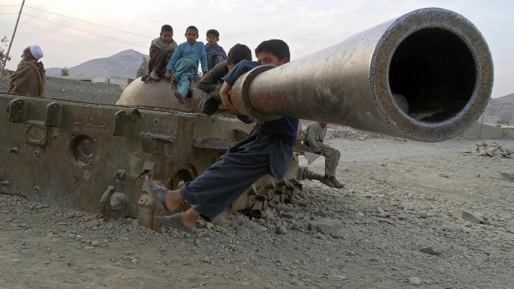 RESTER: Afghanske barn leker ved restene av en sjovetstridsvogn i Behsood-omr�det. Foto: AP / Rahmat Gul / NTB scanpix