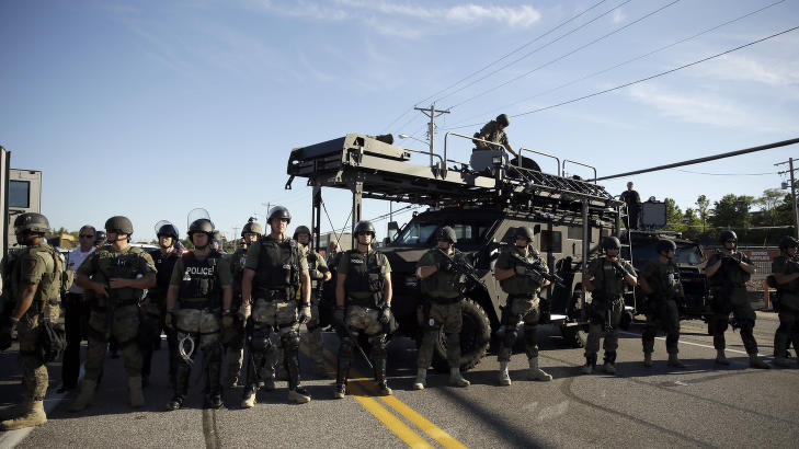 TUNGT BEV�PNET: Tungt bev�pnet politi gjorde seg klare for en fjerde kveld med store demonstrasjoner i Ferguson i Missouri etter at ubev�pnede Michael Brown (18) ble skutt og drept av politiet l�rdag. Foto: AP Photo/Jeff Roberson