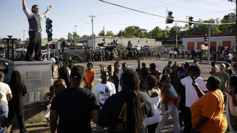 SINTE: En mann fors�ker � roe ned en gruppe demonstranter mens politiet i Ferguson st�r oppstilt i bakgrunnen. Foto: AP Photo/Jeff Roberson