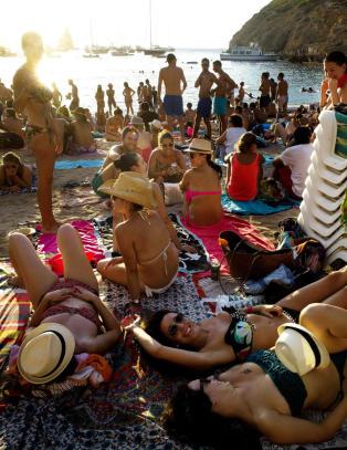 Til slutt sitter, st�r, danser og ligger folkemengden tett i tett i strandkanten