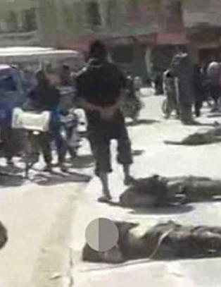 Byens innbyggere, menn, kvinner og barn, g�r forbi, tvunget til � la IS-terroristenes grufulle maktdemonstrasjon v�re en del av dagliglivet