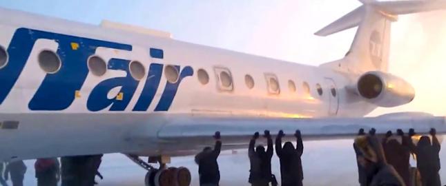 I 44 minusgrader pr�ver passasjerene � dytte l�s flyet