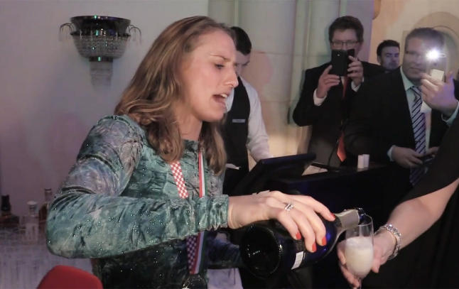 Se Camilla synge, samtidig som hun deler ut champagne