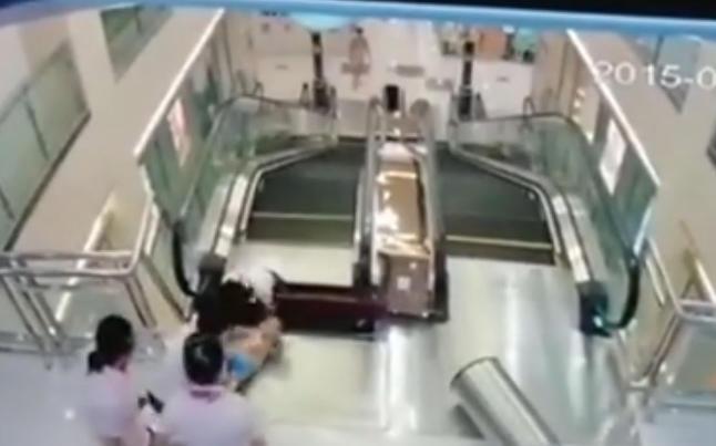 Kvinne blir dratt i d�den av rulletrapp, men rekker � redde s�nnen