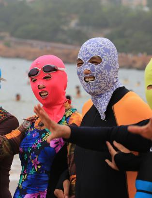 Kinesiske kvinner drar p� seg en �facekini� n�r de skal p� stranda. Oppfinneren innr�mmer et problem