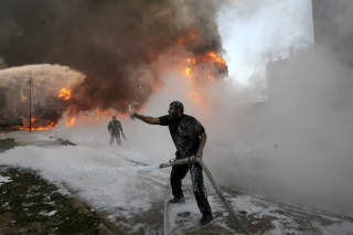 RAMMET SIVILE MÅL: Her forsøker palestinske brannmenn å redusere skadene etter at en israelsk bombe har truffet et kjøpesenter. Foto: AP Photo/Xinhua/Scanpix