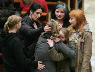 I SORG:  De overlevende etter skoleskytingen omfavner hverandre i kirken i Winnenden i går. AP Photo / Michael Probst