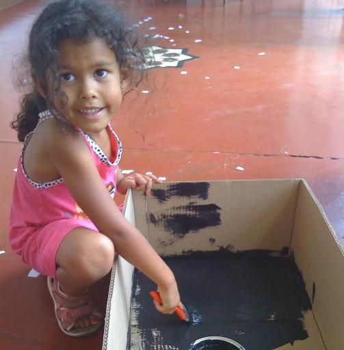 ENKEL OPPFINNELSE: Her hjelper Amina til med � male en Kyoto Box. Foto: privat.