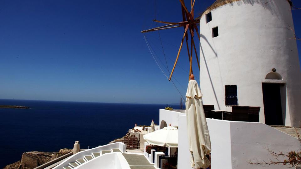 SOL: Turister soler seg i byen Oia på den spetakulære øya Santorini. Foto: Louisa Gouliamaki/Scanpix