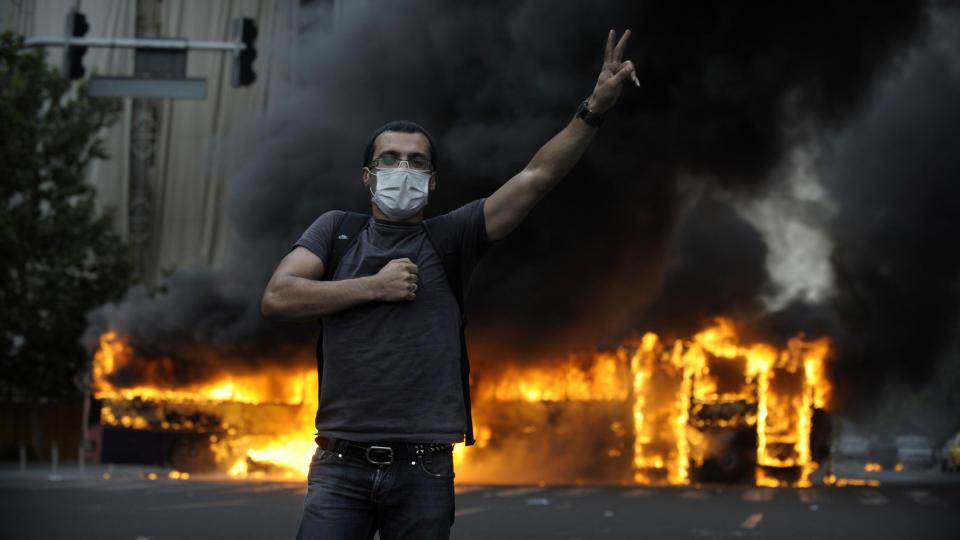- N�DD KOKEPUNKTET: En demonstrant st�r foran en brennende buss i Teherans gater. Iran opplever n� de st�rste oppt�yene siden den islamske revolusjonen i 1979, etter beskyldninger om at president Ahmadenijad kuppet valget. Foto: SCANPIX/AFP PHOTO/OLIVIER LABAN-MATTEI