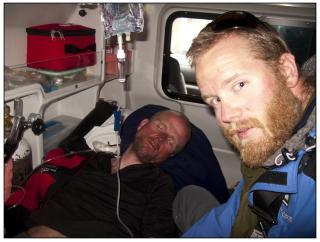 TIL KATMANDU: P� grensa til Nepal sto en ambulanse klar for � frakte Jarle Tr� til sykehuset i hovedstaden. Lege og klatrekollega Lars Oma Erichsrud overv�ker Tr� i ambulansen.