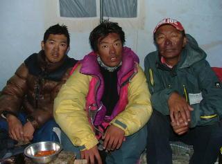 F�RSTE REDNINGSFORS�K:  Jangbu Sherpa (fra venstre), Lhakpa Sherpa og Nawang Tenzing Sherpa er utkj�rte etter at de gikk opp igjen til 8300 meter bare to d�gn etter at de hadde st�tt p� toppen. Her er de nettopp kommet tilbake og sitter i kj�kkenteltet p� 6400 meter. De ble lovet 2500 dollar hver fra Stein Gr�nner�e for � lete etter Jarle Tr�.