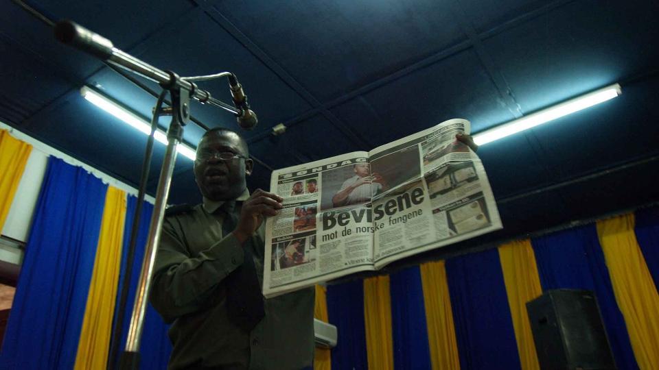 MENER NORSK PRESSE HAR GODKJENT BEVISENE: Aktor, Jean-Blaise Bwamalundu, holder opp et eksemplar av VG i retten. Foto: TORGEIR KROKFJORD/DAGBLADET