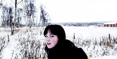 Vil lære: Karina Jacobsen vil gjerne lære kvensk, men vet ikke hvem hun skal snakke det med. Bak ligger Kventunet. Den røde bygningen er et kvensk hus som har blitt flyttet fra Tornedalen i Sverige.